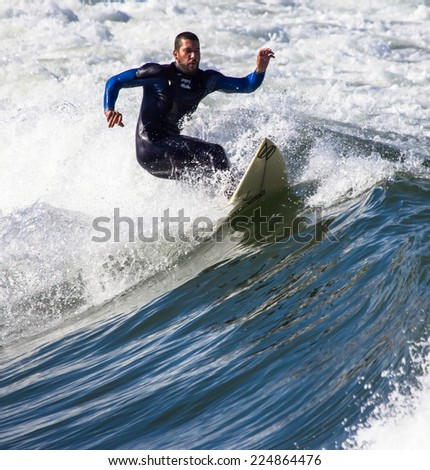 GIJON, SPAIN  Oct, 2014:  Athlete surfing on San Lorenzo beach located in Gijon, in the north of Spain. October 17, 2014 - stock photo