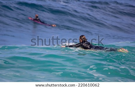 GIJON, SPAIN  Sep, 28:  Unidentified men surfing on a beach located on the outskirts of Gijon. Spain. September 28, 2014 - stock photo
