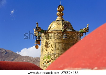 Gilded dhvaja-victory banner with makaras on the red rooftop of  the AD.642 founded-25000 m2 Jokhang-House of Buddha temple. Lhasa-Tibet. - stock photo