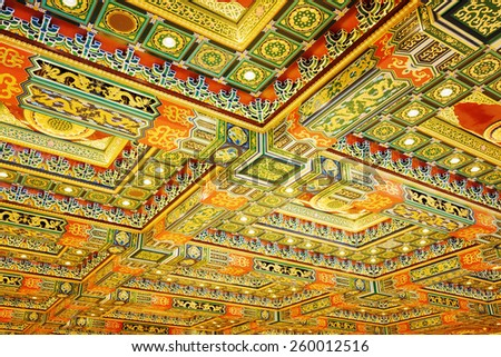 Gilded red patterns on the ceiling in interior of the temple, Po Lin Monastery at Lantau Island, in Hong Kong. Hong Kong is popular tourist destination of Asia. - stock photo