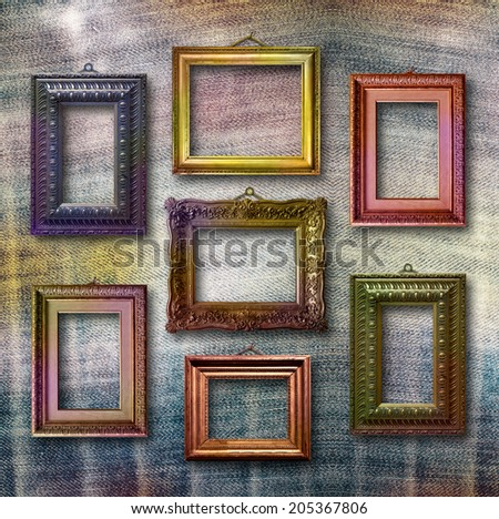 Gilded wooden frames for pictures on blue jeans background - stock photo