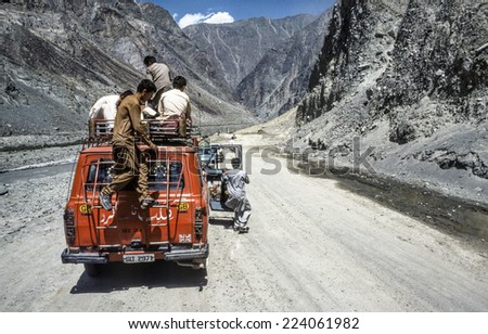 GILGIT, PAKISTAN - JUNE 30, 1987: people on a car stop because of a landslide in Gilgit, Pakistan. The Karakoram Highway is the only street to china and often interrupted by landslides. - stock photo