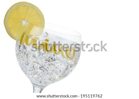 Gin and tonic in a highball cup garnished with a lemon wedge and twist - stock photo