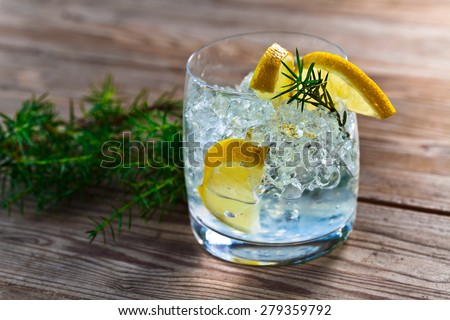 gin and tonic with lemon and ice on wooden table - stock photo
