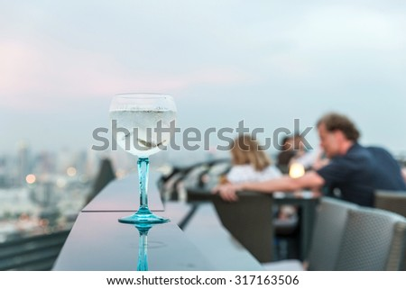 Gin tonic cocktail on table in rooftop bar - stock photo