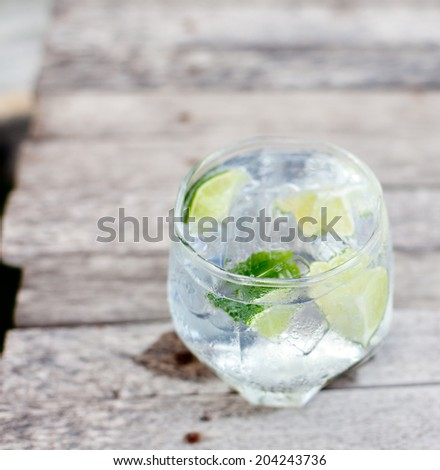 Gin tonic in glass with ice and lime slice on a wooden background. Selective focus. - stock photo
