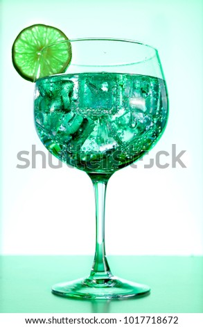 Gin tonic with lime slice  on green background