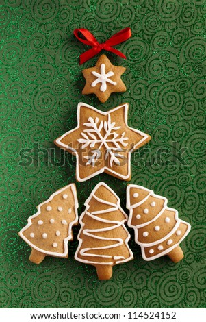 Ginger and Honey cookies in the shape of a Christmas fir tree and snowflake with white sugar decoration and bows on the green texturized paper background.