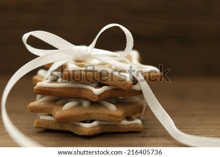 Ginger Bread Cookies with white Ribbon and Bow on Wood with Copy Space - stock photo