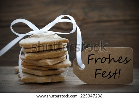 Ginger Bread Cookies with white Ribbon and Label with the German Words Frohes Fest, which means Merry Christmas - stock photo