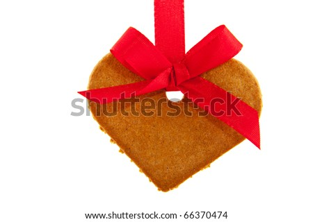 Ginger bread heart hanging at red ribbon isolated over white