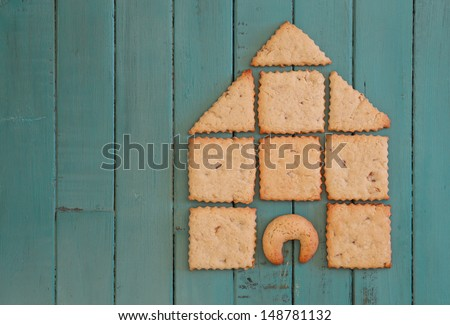 Ginger Cookies Stacked as house on turquoise wooden board, copy space - stock photo