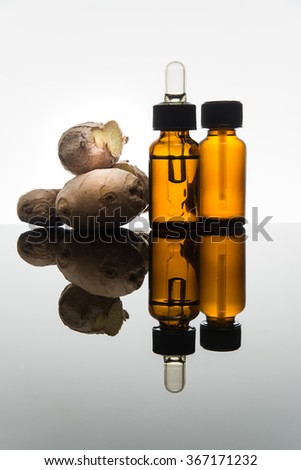 Ginger essential oil in amber glass bottle with ginger root and dropper - stock photo