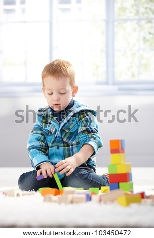 Ginger-haired toddler playing on floor with building cubes. - stock photo