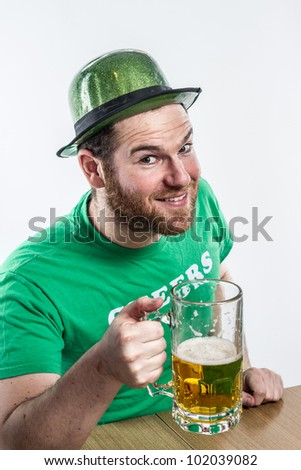 Ginger Irish man toasting on Saint Patrick's day in green hat clothes yellow pilsner large glass mug
