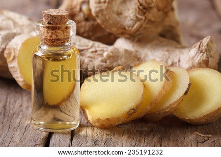 ginger oil in a glass bottle close-up, against the background of the root. horizontal
