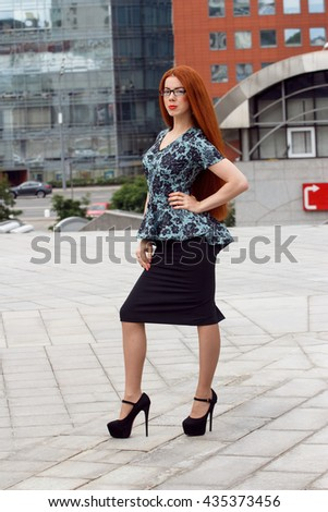 Ginger smiling business woman posing on urban background