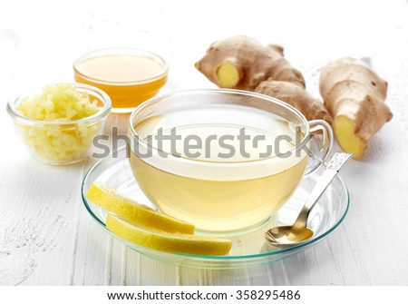 Ginger tea and fresh ginger root on white wooden background - stock photo