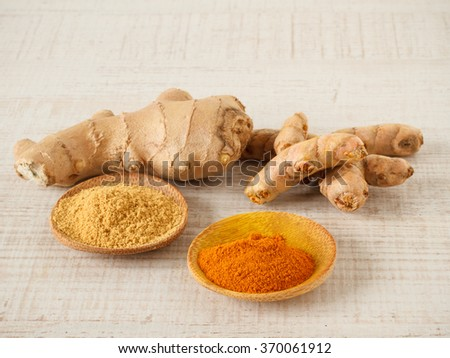 Ginger , turmeric powder and root on a table - stock photo