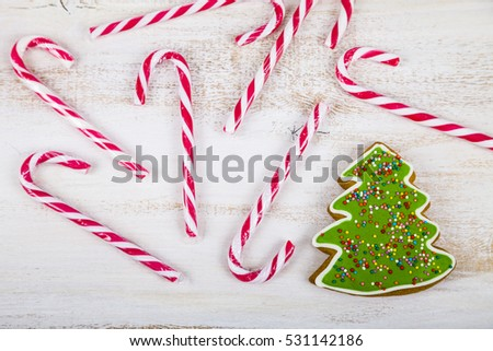 Gingerbread and candy canes on a wooden background. Christmas sweets and decorations