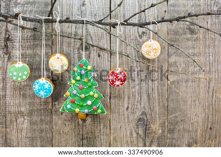 gingerbread christmas tree with cookies hanging over aged wooden background - stock photo