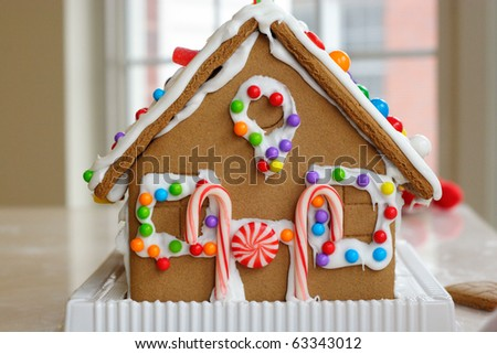 Gingerbread cookie house dotted with colorful candy - stock photo
