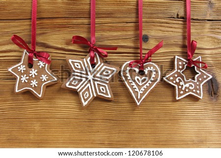 Gingerbread cookies hanging on wooden background. Christmas decoration.