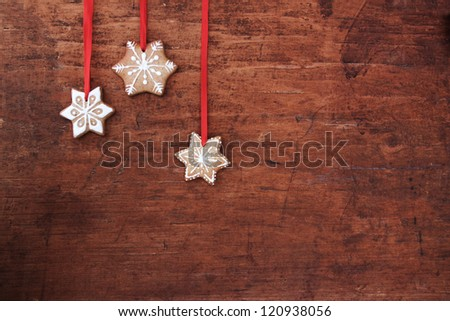 Gingerbread cookies hanging over wooden background. - stock photo