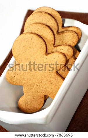 gingerbread cookies in a white dish with gold background