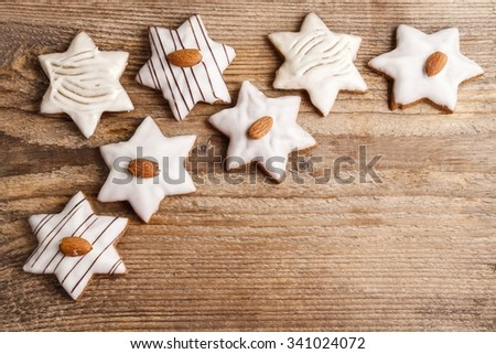 Gingerbread cookies in star shape decorated with almonds on brown wooden background, copy space - stock photo