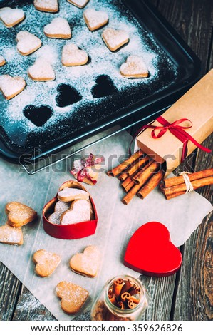 Gingerbread cookies in the shape of a heart in gift on Valentine's day.Box in the shape of a red heart on a wooden table. Gingerbread cookies and cinnamon sticks dusted with white powder.