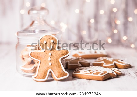 Gingerbread cookies on a table and Christmas lights on background - stock photo