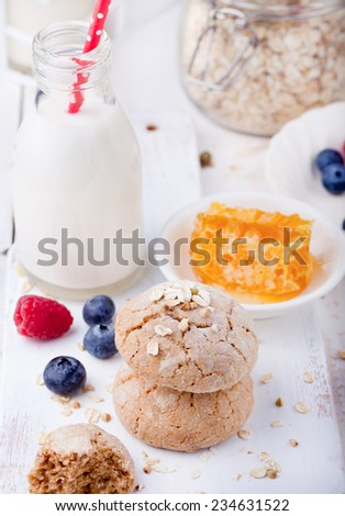 Gingerbread cookies with fresh berries and bottle of milk on a white wooden background - stock photo