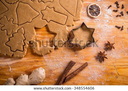 Gingerbread dough with various shapes and a cutter.