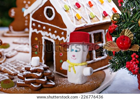 Gingerbread house and a snowman from marshmollow  - homemade Christmas cookies - stock photo
