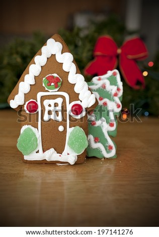 Gingerbread house and gingerbread Christmas tree on a table. - stock photo