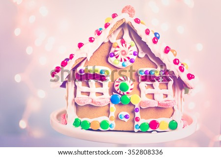 Gingerbread house decorated with white royal icing and bright candies. - stock photo