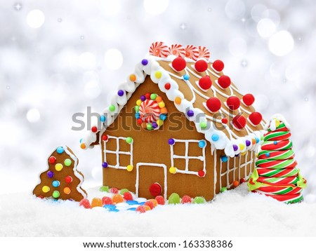 Gingerbread house in snow with twinkling silver light background - stock photo