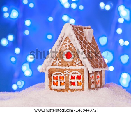 Gingerbread house in the snow with a beautiful New Year's background - stock photo