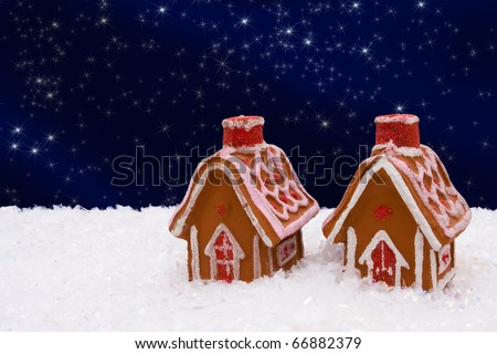 Gingerbread house on snow with a night sky background - stock photo