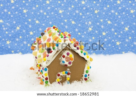 Gingerbread house on snow with star background, gingerbread house - stock photo