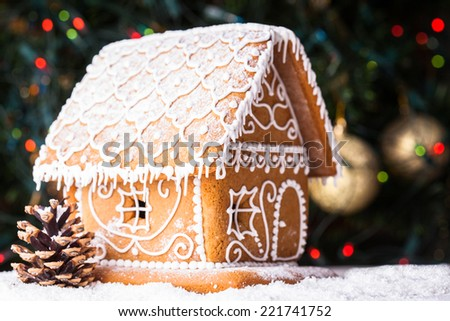 gingerbread house over defocused lights of Chrismtas decorated fir tree - stock photo