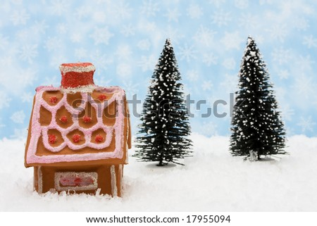 Gingerbread house with an evergreen tree on snow with snowflake background, Merry Christmas - stock photo