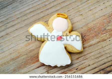 Gingerbread in a shape of angel with white icing on wooden table - stock photo