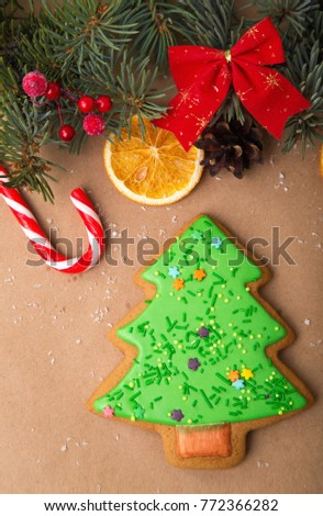 Gingerbread in the form of a New Year tree. Christmas homemade gingerbread on a wooden table. Gingerbread, sweets, dried orange, candied fruit - traditional Christmas decor.