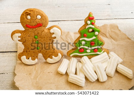 gingerbread man and Christmas tree in the snowy pile of marshmallows on parchment on white wood  background