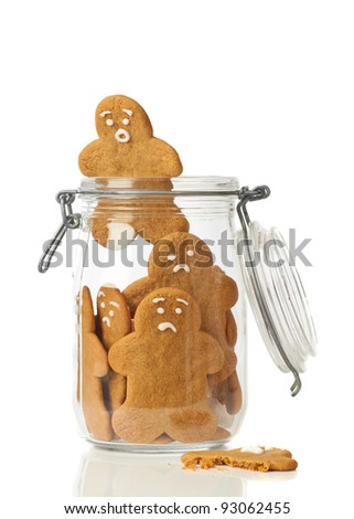 Gingerbread man escaping the jar of cookies on white background - stock photo