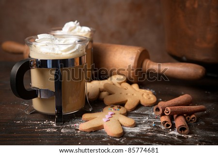 Gingerbread men cookie biscuits with hot coffee and whipped cream - stock photo