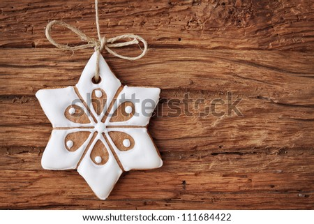 Gingerbread snowflake hanging over wooden background - stock photo