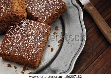Gingerbread sprinkled with powdered sugar on vintage pewter plate with rustic wood background.  Low key still life with directional natural lighting.